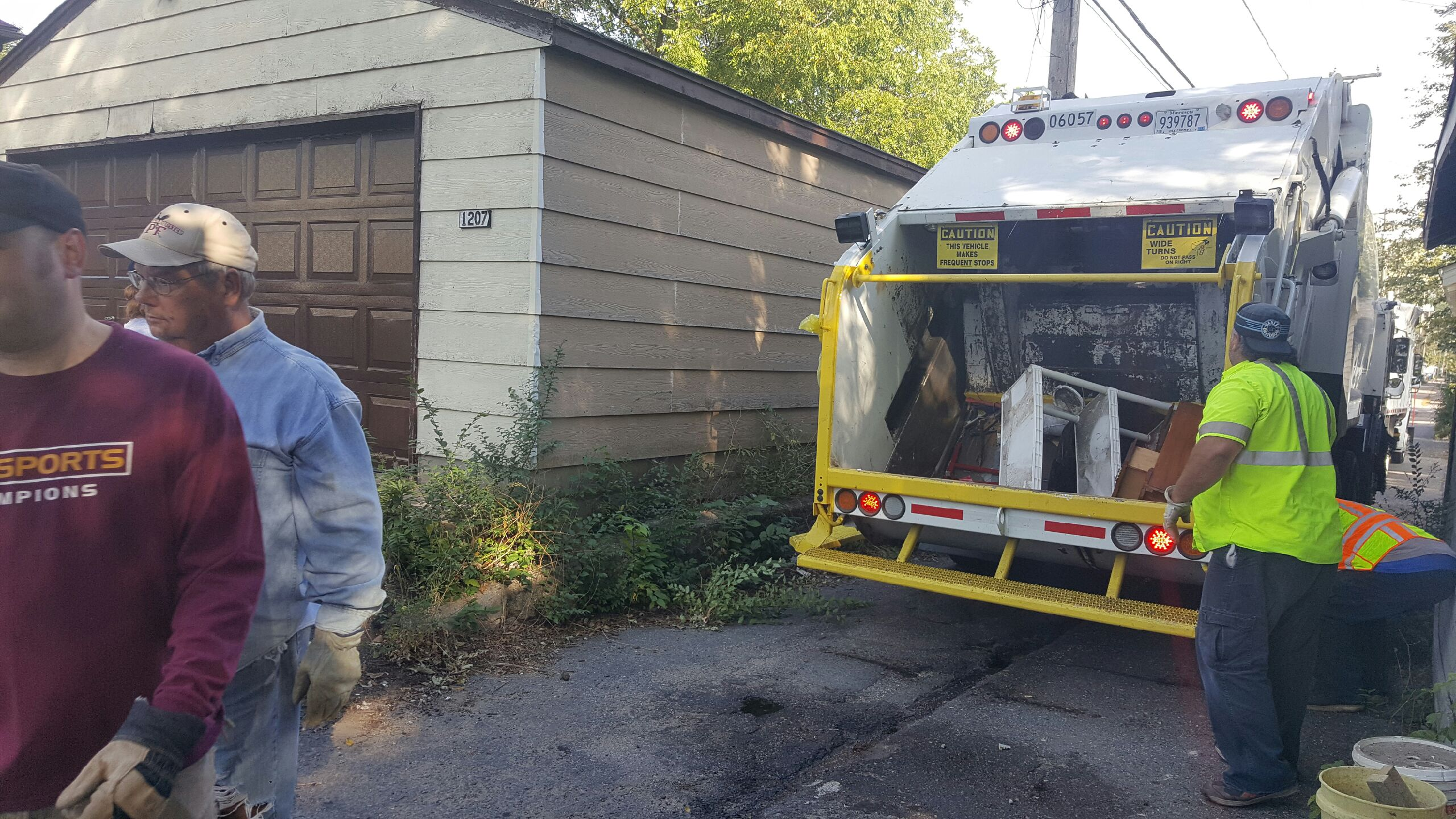 A garbage truck picking up refuse in an alley