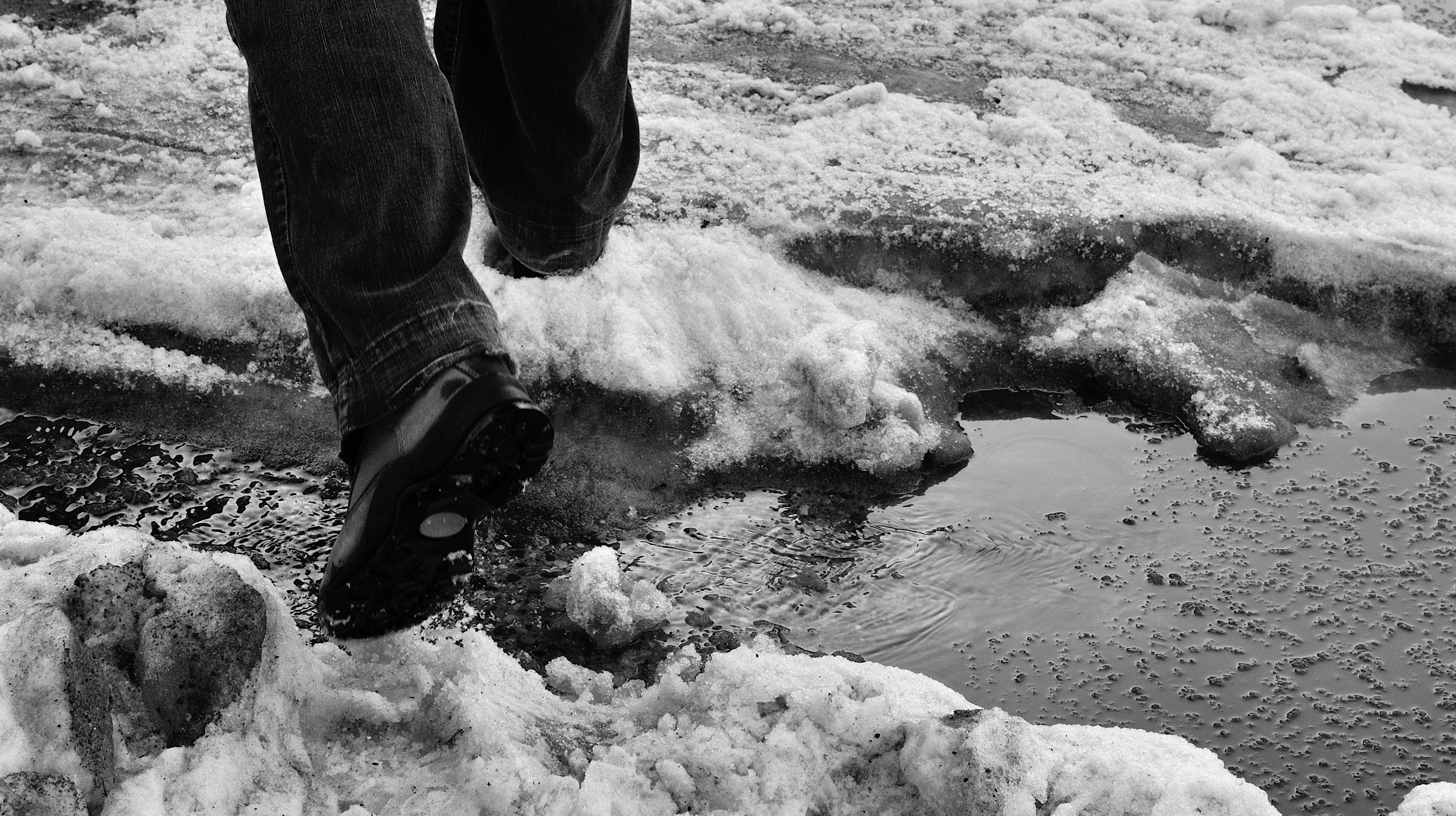 A person walking through sludge and snow