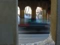 View from sidewalk through arches of bridge