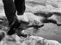 A person walking through sludge and snow
